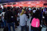 Decenas de personas hacen fila en la zona de 'check-in' de Avianca para revisar el estado de sus vuelos.