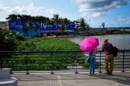 """Dos visitantes del Gran Malecón observan el panorama que ofrece el escenario, de cara al barrio Siape. En un gran mural se lee """"Vive el espacio público""""."""