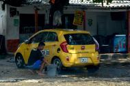 Un joven lava un taxi en la vía pública en la Ciudadela 20 de Julio, sur de Barranquilla.