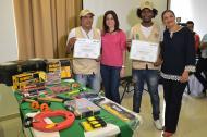 La secretaria de Desarrollo, Madeleine Certain, y la primera Gestora, Katia Nule, entregan certificados a dos beneficiarios del programa.