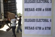 Trabajadores descargan material electoral para ubicarlas en el estadio Nacional en Santiago, con miras a las elecciones para elegir presidente y senadores durante la jornada prevista para mañana.
