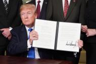 Donald Trump muestra la resolución tras su firma, ayer en la Casa Blanca.