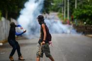 Dos jóvenes responden contra agentes del gobierno de Nicaragua, en Masaya.