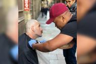 Léwinson Castro le corta el cabello y la barba a un habitante de la calle en Barcelona, España.