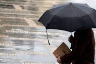 Un hombre sujeta un paragua mientras llueve.