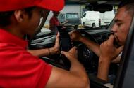 Un empleado de la gasolinera le muestra el datáfono a un cliente que acaba de tanquear su vehículo.