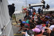 Los migrantes hondureños que se dirigen en una caravana a los EE.UU. suben la entrada del puente fronterizo internacional Guatemala-México en Ciudad Hidalgo.