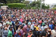 Migrantes hondureños que se dirigen en caravana a Estados Unidos se renieron este viernes en el parque central de Ciudad Tecún Uman, Guatemala, en la frontera con México.