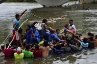 Algunos cruzan el río Suchiate en una balsa con la esperanza de continuar su camino a EEUU.