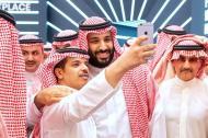 Mohamed bin Salmán se toma una selfie con una persona no identificada antes de la inauguración del foro internacional sobre inversión (FII) organizado en Riad,