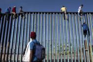 Algunos migrantes escalan el muro que divide Tijuana con San Diego.