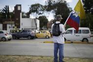 Un ciudadano sostiene la bandera de Colombia con el símbolo de la paz.