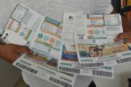 Un residente del barrio Olaya, que pertenece al nivel socioeconómico del estrato 3, muestra el registro de sus facturas de energía.