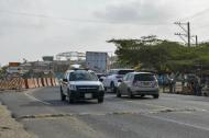 Varios vehículos transitan por la vía Barranquilla-Ciénaga. En la parte de atrás se observan las obras del puente Pumarejo.