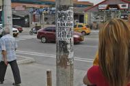 Una mujer espera el bus cerca de un poste que tiene varios avisos pegados.