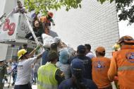 Momento en que miembros de la Policía, Bomberos y Defensa Civil evacúan a pacientes.