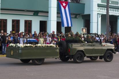 Cubanos saluda al paso de la caravana con la urna.