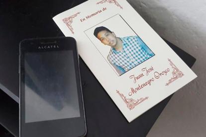 Por este celular Alcatel un asaltante mató a Juan. Al lado, una tarjeta fúnebre dedicada a su memoria