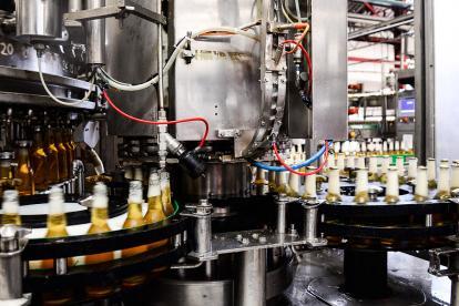 La máquina llenadora ejecuta el proceso de llenado y tapado.