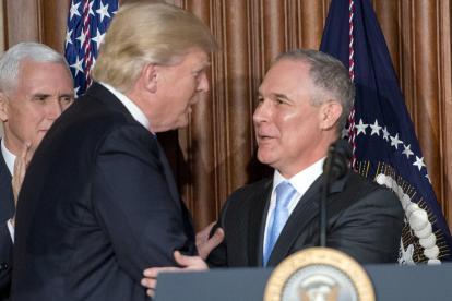 El presidente Donald Trump es saludado por el encargado del medioambiente, Scott Pruitt.