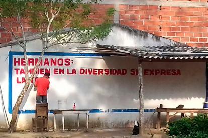Un trabajador cambia el mensaje original del mural en el barrio Las Américas.