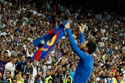 Messi celebra el tanto del triunfo del Barcelona en el Bernabéu mostrando su nombre en la camiseta, mientras algunos hinchas lo insultan.
