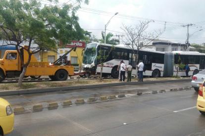 Una grúa moviliza uno de los buses de Transmetro relacionados al choque.