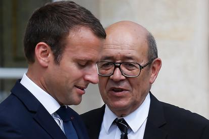 El presidente francés, Emmanuel Macron, izq., habla con el ministro de Relaciones Exteriores, Jean-Yves Le Drian.