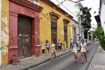 Turistas caminan por una de las calles del Centro Histórico de Cartagena, en la que se ve una fachada deteriorada.