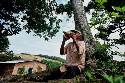 Turibio Anselmo González hace sonidos con su 'celular', una concha de mar. Al fondo está Juaruco, corregimiento de Tubará.