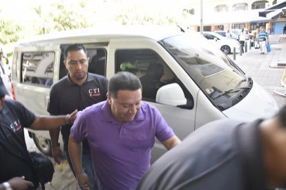 Agentes del CTI de la Fiscalía acompañan al suspendido mandatario Duque, a su ingreso al complejo judicial.