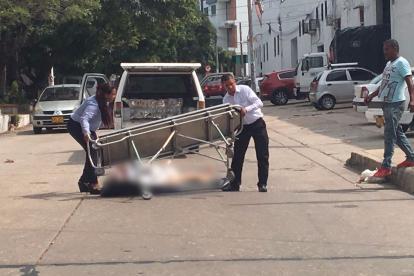 Trabajadores de la funeraria recogen el cuerpo que quedó tendido en plena vía.