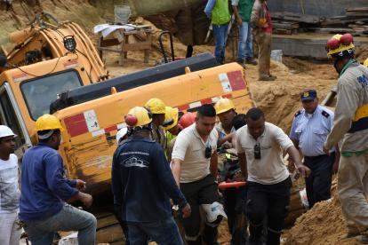 Bomberos rescatan a uno de los obreros que resultó atrapado por el alud de tierra.