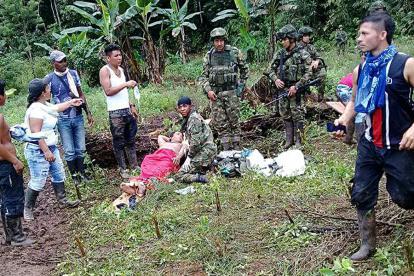 Varios soldados y campesinos atienden a una de las personas que resultó herida en el ataque en Tumaco.