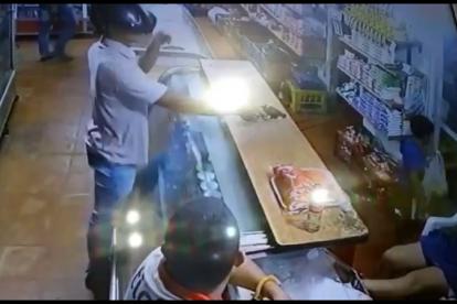 Momento en que uno de los asaltantes apunta contra propietarios de la tienda.