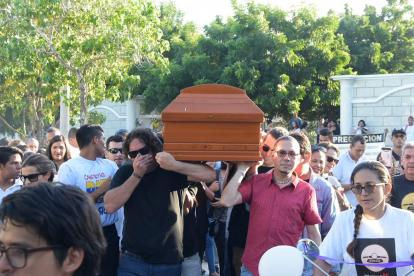 Decenas de personas se reúnen en el lugar donde se realizan las honras fúnebres.