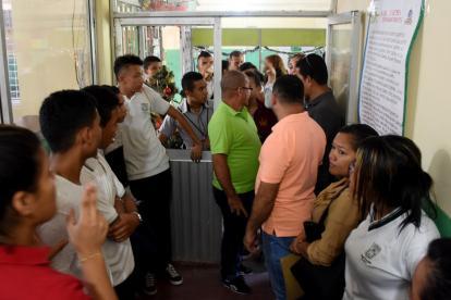 Estudiantes y padres de familia en el colegio reclamando por la pérdida del año escolar.