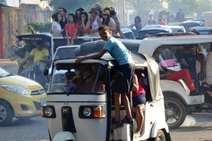 Menor agarrado al techo de la motocarro durante caravana en Soledad.