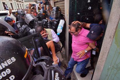 El candidato a la Presidencia por la Farc, Rodrigo Londoño, es escoltado en Cali mientras desde afuera le lanzan huevos.