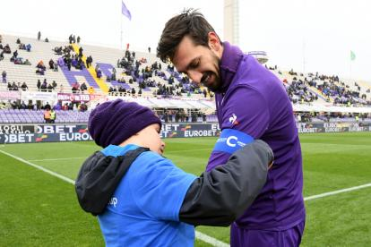 Un niño le coloca la cinta de capitán a Davide Astori antes de iniciar un juego de la Fiorentina.