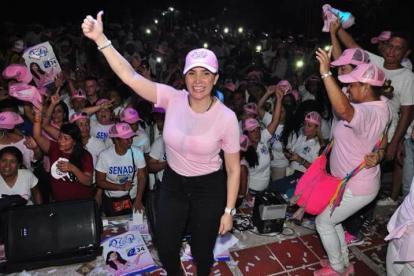 La congresista Aida Merlano alza el brazo en señal de victoria, en el cierre de un acto político.