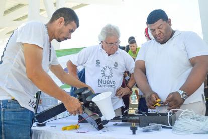 El alcalde de Soledad, Joao Herrera, entrega los equipos a dos representantes de un frente de seguridad.