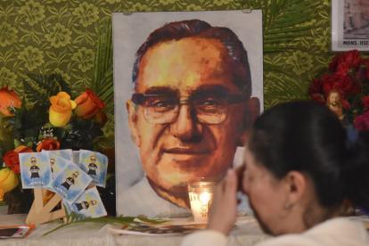 Una seguidora llora en una pintura de San Óscar Romero.