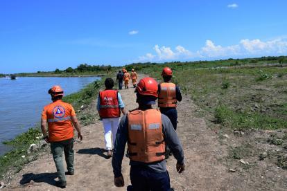 Miembros de la Defensa Civil y bomberos realizan la búsqueda vía terrestre.
