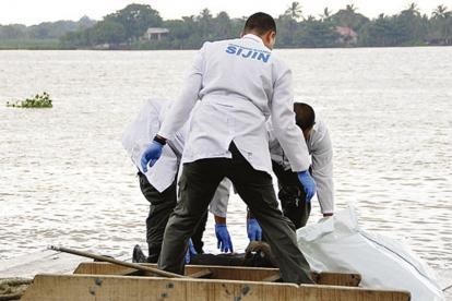 Peritos de la Sijín en una diligencia de levantamiento de cadáver junto al río.