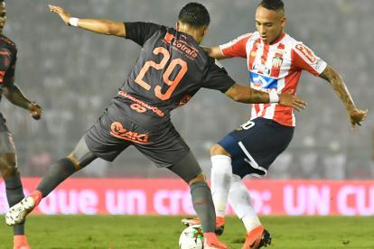 Jarlan Barrera cubriendo el balón ante la marca del lateral Sebastián Macías.