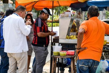 Barranquilleros consumen empanadas y patacones en la esquina de la carrera 52 con calle 76.