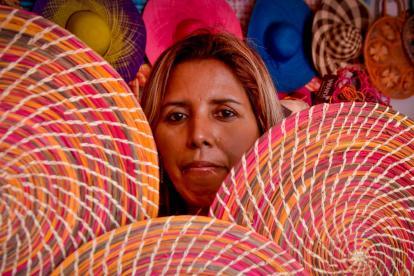 Una artesana exhibe los productos artesanales hechos a mano en palma de iraca.