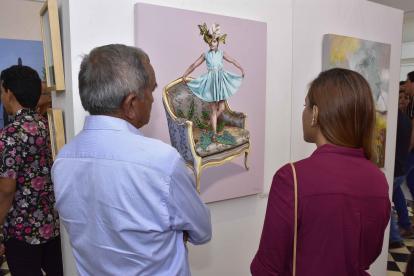 Dos asistentes a la exposición aprecian la obra del artista barranquillero Omar Mendoza.