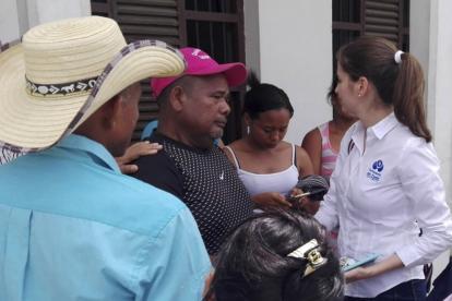 Manuel Berrío (de gorra rosada), compañero sentimental de María del Pilar Hurtado, habla con Ana Sánchez, defensora del Pueblo.